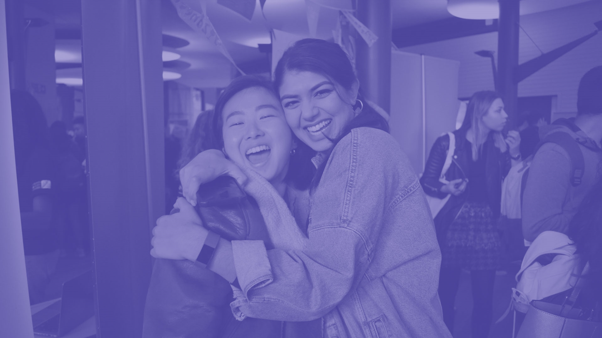 Two students smiling and hugging each other
